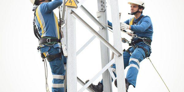 homes traballando nunha torre de electricidade