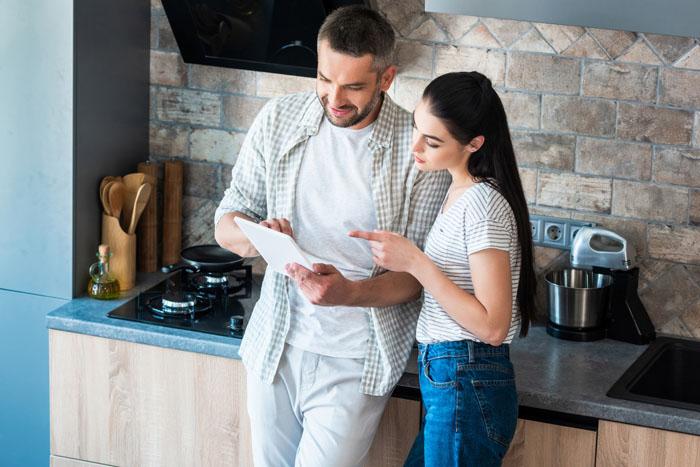un hombre y una mujer ojeando una tablet